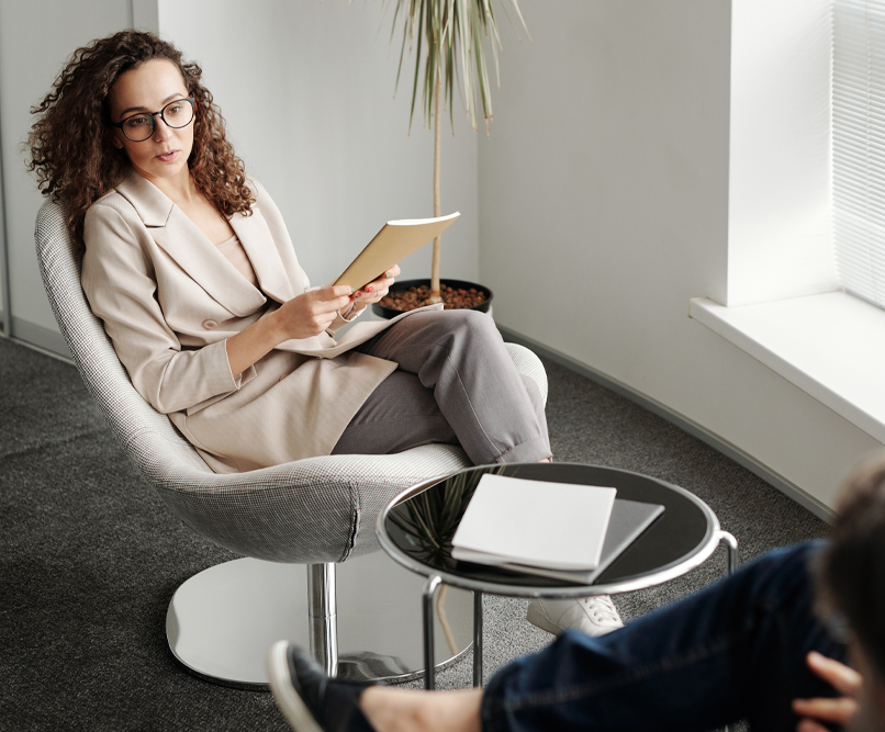 A woman sits in a chair holding a notebook. She is talking to a man who sits across from her.