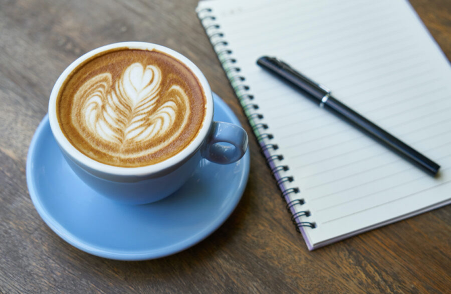 A cappucino in a cup and saucer is sat next to a lined notebook on a bare wood table.