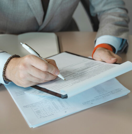 A close up of a businessman's hands filling in a form
