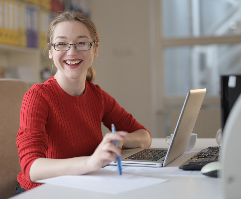 A woman in a red jumper and glasses is smiling at the viewer. In front of her is an open laptop.