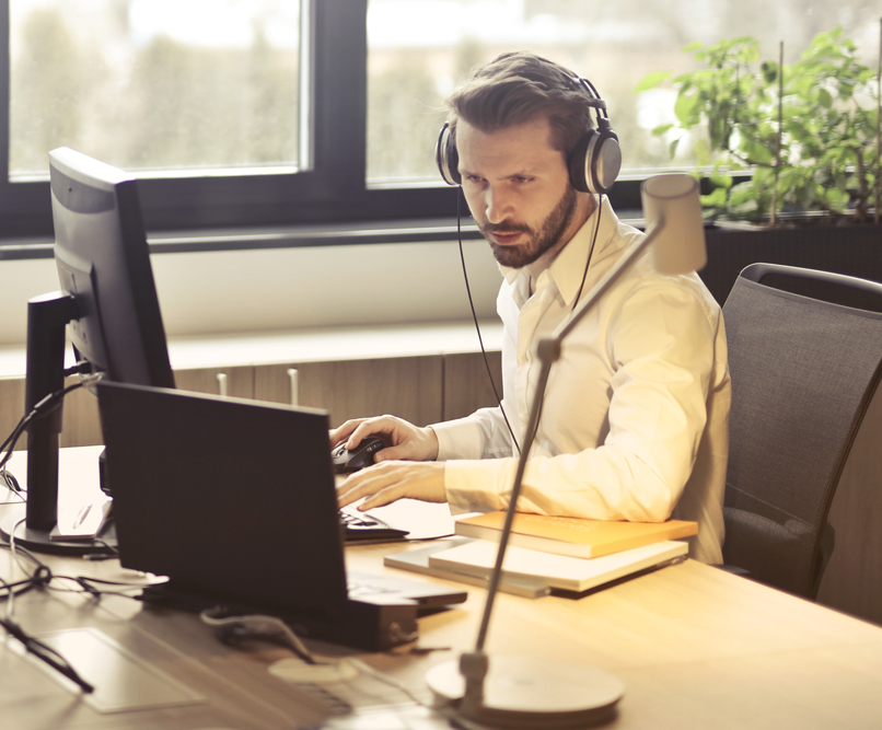 A man working at a laptop wearing a headset.