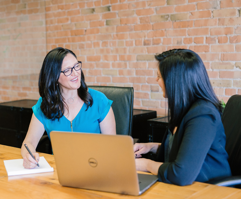 Two business women are having a conversation. Next to one of the women is an open laptop.