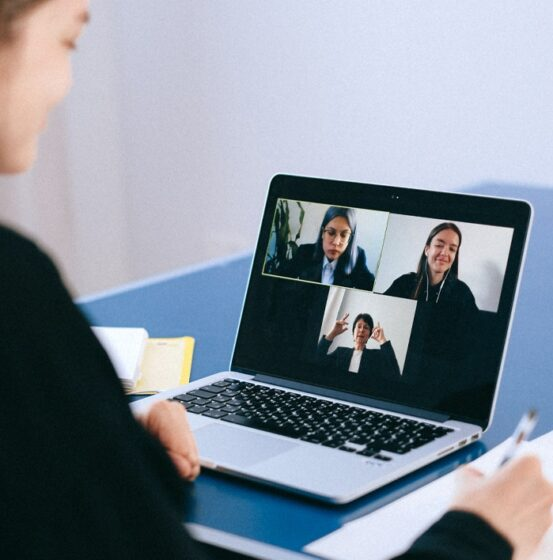 A woman is video calling three other business women.
