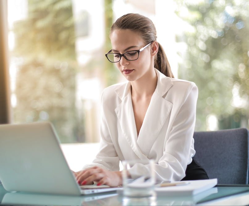 A woman with glasses works at a laptop.