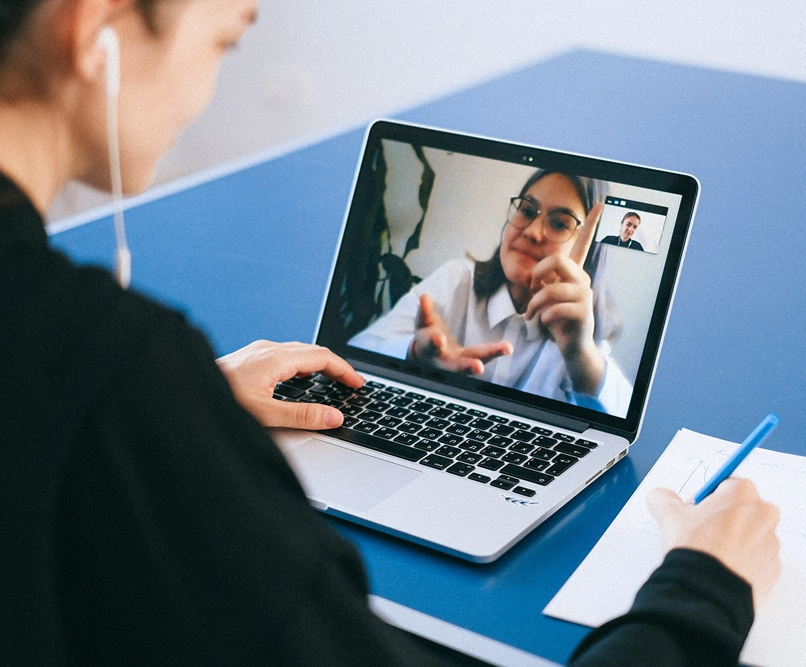 A women is talking to a medical professional through a virtual meeting on the computer. The medical professional is a women wearing glasses. She is gesturing as she speaks while the women watching is taking notes on a notepad.